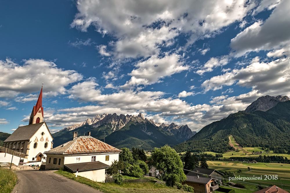 Aufkirchen, una vista del santuario di Santa Maria e della vallata con le Dolomiti sullo sfondo
